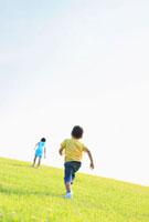草原を走る日本人の男の子と女の子