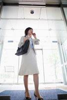 携帯電話で話す日本人のビジネスウーマン
