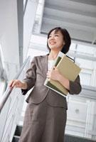 ファイルを持った日本人のビジネスウーマン 10272000785  写真素材・ストックフォト・画像・イラスト素材 アマナイメージズ