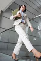 ファイルを持って歩くビジネスウーマン 10272000810  写真素材・ストックフォト・画像・イラスト素材 アマナイメージズ