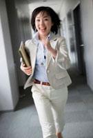 ファイルを持って走るビジネスウーマン 10272000811  写真素材・ストックフォト・画像・イラスト素材 アマナイメージズ