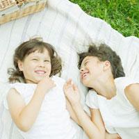 シートに寝転がるハーフの姉妹 10272000860| 写真素材・ストックフォト・画像・イラスト素材|アマナイメージズ