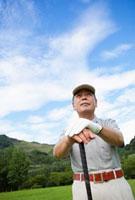 ゴルフをする日本人シニア男性