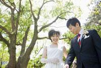 新緑の下で笑う日本人の新郎新婦