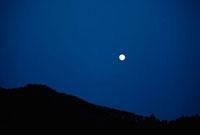 夜空に浮かぶ月と山