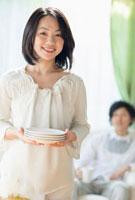 皿を持った女性とソファに座る男性