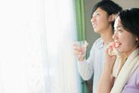 窓辺で汗を拭く女性とコップを持つ男性