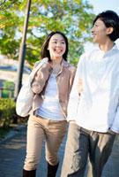 エコバックを持ち腕を組んで歩くカップル