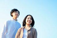 青空の下にたたずむ日本人カップル