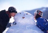 雪だるまにキスをする日本人の子供