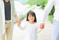 父母と手を繋ぐ日本人の女の子