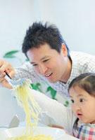 パスタを持ち上げる日本人の父と娘