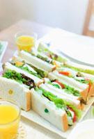 食卓に並ぶサンドイッチとオレンジジュース