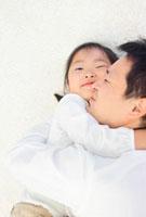 寝転んで抱き合う日本人の父と娘