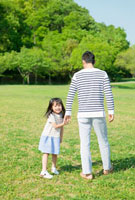 公園で手を繋ぐ父と娘