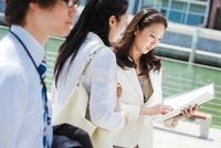 資料を見ながら話す2人の女性とビジネスマン