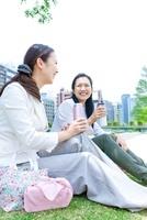 タンブラーを持って芝生に座る2人の女性