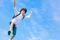 両手を挙げてジャンプする小学生の男の子