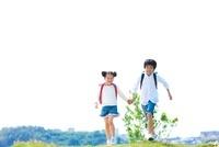 ランドセルを背負って走る小学生の兄妹