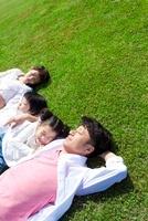 草原に寝転ぶ日本人家族