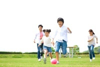 ボールを追いかけて遊ぶ日本人家族
