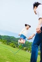 縄跳びをして遊ぶ日本人の父と娘