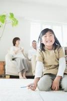 リビングでお絵描きをする娘とソファに座る両親