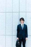 鞄を持って立つ日本人ビジネスマン