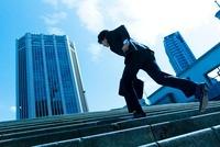階段を駆け上る日本人ビジネスマン
