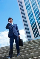 階段に立ち携帯電話で話す日本人ビジネスマン