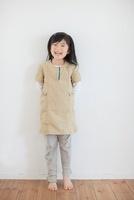 壁の前に立って笑う日本人の女の子 10272002180  写真素材・ストックフォト・画像・イラスト素材 アマナイメージズ