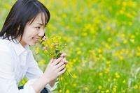 花の香りを嗅ぐ日本人女性