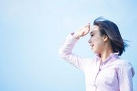 手で日差しを避ける日本人女性