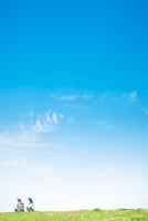青空の下で草原に座る女性2人の遠景