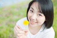たんぽぽの花を持つ日本人女性
