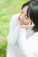 頬杖をついて目を閉じる日本人女性