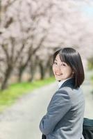 桜並木と振り向く日本人ビジネスウーマン 10272002370  写真素材・ストックフォト・画像・イラスト素材 アマナイメージズ