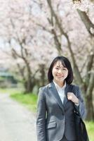 桜の木の下で笑う日本人ビジネスウーマン 10272002373  写真素材・ストックフォト・画像・イラスト素材 アマナイメージズ