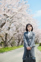 桜並木の前に立つ日本人ビジネスウーマン