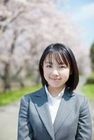 桜並木の前で微笑む日本人ビジネスウーマン 10272002378  写真素材・ストックフォト・画像・イラスト素材 アマナイメージズ