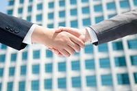 ビルの前で握手をする手