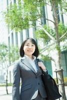 ビル街に立つ日本人のビジネスウーマン
