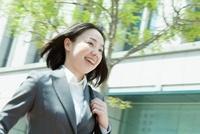ビル街を走る日本人のビジネスウーマン 10272002388  写真素材・ストックフォト・画像・イラスト素材 アマナイメージズ