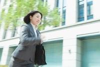 ビル街を走る日本人のビジネスウーマン
