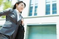 ビル街を走る日本人のビジネスウーマン 10272002390  写真素材・ストックフォト・画像・イラスト素材 アマナイメージズ
