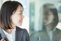 ガラス越しに見つめる日本人ビジネスウーマン 10272002419  写真素材・ストックフォト・画像・イラスト素材 アマナイメージズ