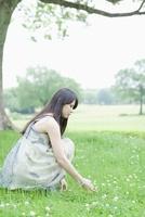 草原に座る日本人女性 10272002493  写真素材・ストックフォト・画像・イラスト素材 アマナイメージズ