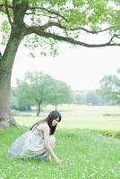 草原に座る日本人女性 10272002506  写真素材・ストックフォト・画像・イラスト素材 アマナイメージズ