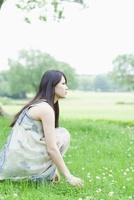 草原に座る日本人女性 10272002508  写真素材・ストックフォト・画像・イラスト素材 アマナイメージズ