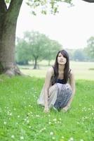 草原に座る日本人女性 10272002509  写真素材・ストックフォト・画像・イラスト素材 アマナイメージズ